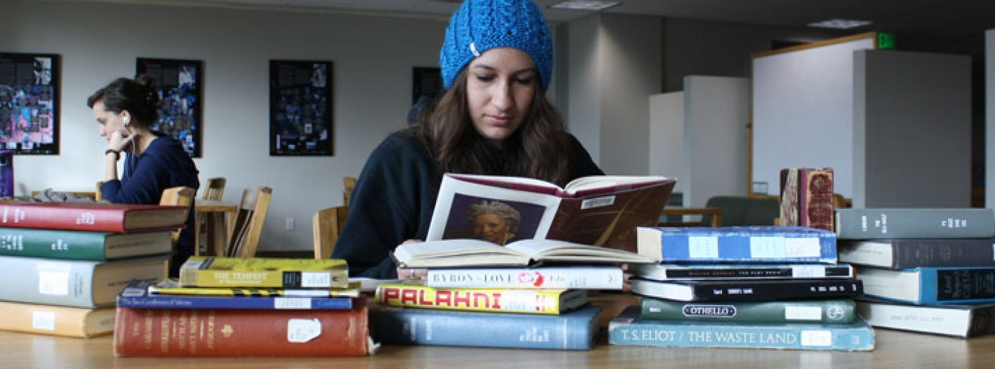 Student reading books at a table in the library.